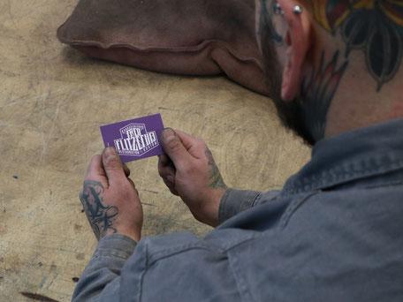 Business Card in Lila Violett. Max hält seine Visitenkarte in der Hand. Projekt: Logo Redesign for Fred Flitzefuß Custom. By Zuni from BRAVE & BUTT DESIGN STUDIO