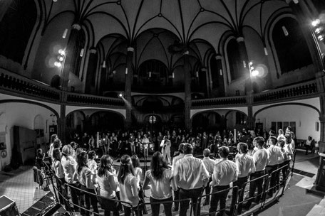 Chor auf der Bühne, Rücken zur Kamera, volles Publikum (s/w)