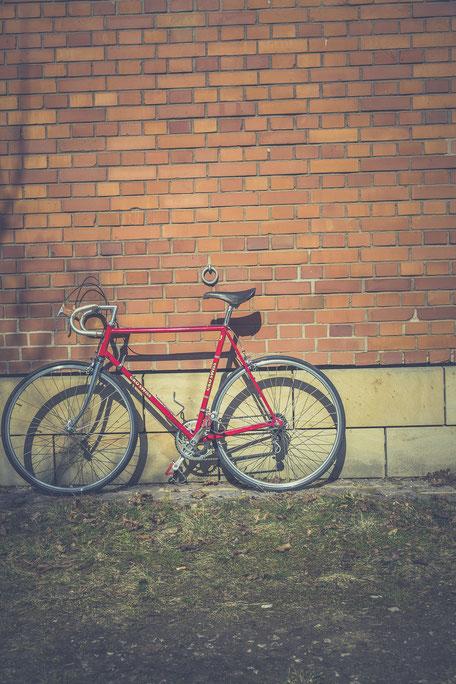 vélo de course rouge sur mur en brique