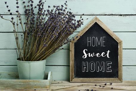 Bild mit einem Schild: Home sweet home, daneben Pflanzen in einem mintfarbenem Eimer