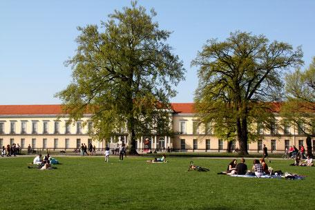 Menschen sitzen auf dem Rasen vor dem Neuen Flügel (Knobelsdorff-Flügel) des Schloss Charlottenburg im Frühling. Foto: Helga Karl