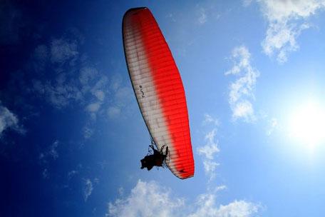 石垣の青空に羽ばたく金城さんのパラグライダー