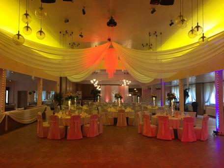 Ambiente-Beleuchtung: rote Scheinwerfer heben den Brauttisch hervor.
