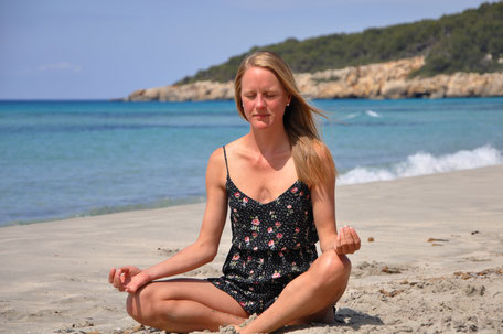 Meditierende Frau bei Sonnenuntergang