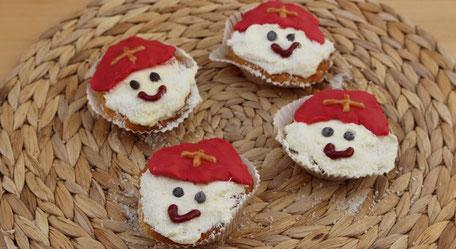 4 kleine Muffins mit Nikolausgesicht (Bart aus Kokosflocken, rote Mitra aus Zuckermasse) liegen auf einer Bastunterlage