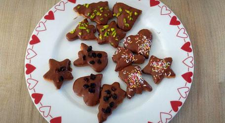 Kleine Lebkuchen mit Rosinen und Pistazien dekoriert liegen in Stern-, Herz-, Tannenbaumform auf einem weißen Teller