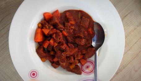 Auf einem weißen Teller sind kleine Fleischstücken und Möhrenstücke in einer braunen Soße zu sehen