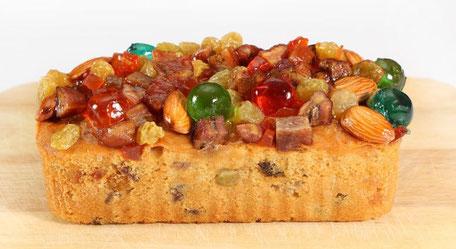 Auf einem Holzbrett liegt ein länglicher Kuchen, der oben drauf mit Nüssen, Früchten und Rosinen dekoriert ist