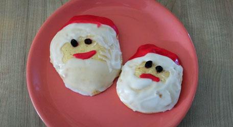 Zwei runde Plätzchen, dekoriert als Nikolaus-Gesichter (mit Rosinen, weißem und rotem Guß) liegen auf einem rosa Teller