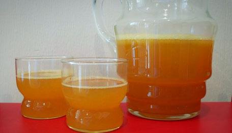 Auf einer roten Ablage stehen 2 Gläser mit einer orangfarbenen Flüssigkeit und rechts daneben befindet sich eine Glaskaraffe