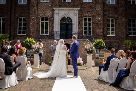 Brautpaar im Freien vor einem Schloss