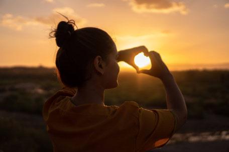 Frau im Sonnenuntergang formt mit den Händen ein Herz
