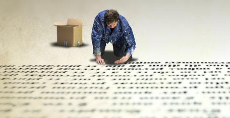 Mann kniet vor einem riesigen handschriftlichen Text.