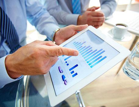 Mann zeigt am Tablett-PC den Chart.