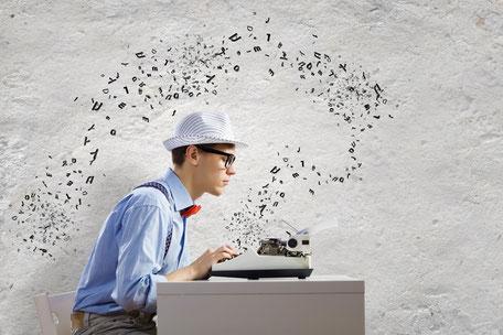 Junger Mann mit Hut schreibt an seiner Schreibmaschine Texte.