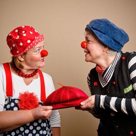 Die Klinikclowns Kiki und Fine zerren an einer roten Mütze. Foto: Andrea Pagels