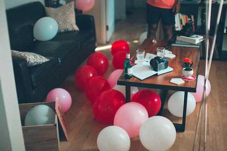 ett vardagsrum med ballonger på golvet