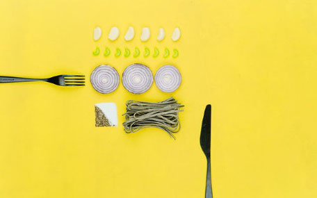 pastaingredienser och bestick med gul bakgrund
