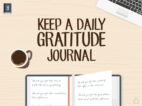 A cup of coffee, gratitude journal and a laptop on a table