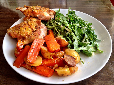 A plate of grilled chicken thigh, roasted carrots and potatoes and a side of rocket salad on a white porcelain plate set against a dark wooden table