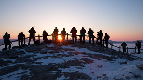 A group of photographers taking a picture of a sunrise from a mountain top