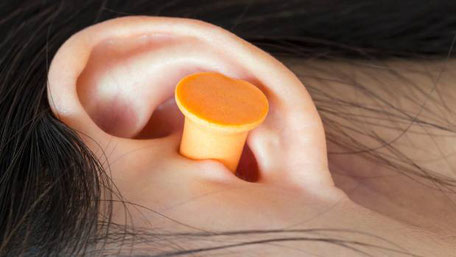 An asian woman using ear plugs to block out unwanted noises while she sleeps