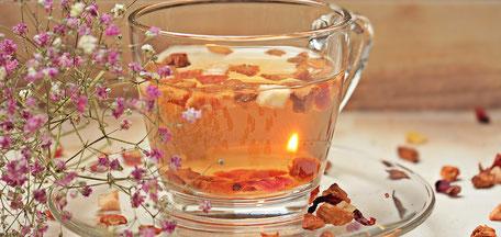 Tee in einer Glastasse. Der Tisch ist mit Blüten bedeckt, links befindet sich ein Blumenstraß.