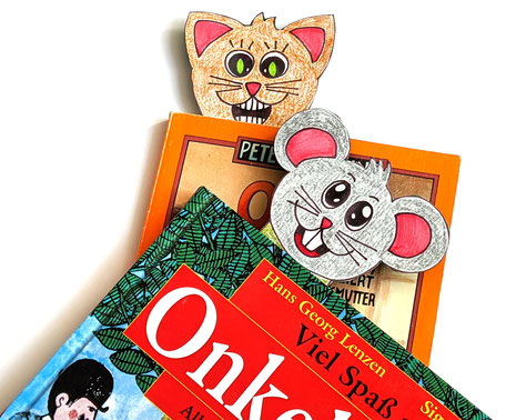 Katz und Maus schauen aus dem Buch: Mit unseren Lesezeichen für Kinder zum Selberbasteln können kleine Bücherwürmer ihre eigenen Buchzeichen gestalten.