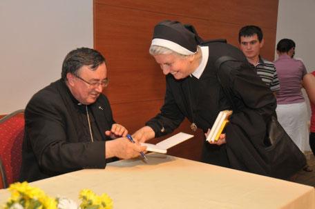 """Kardinal Vinko Puljić potpisiva knjigu """"Moje druge konklave 2013."""" sestri Svjetlani"""