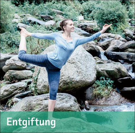 Junge Frau macht Entspannungsübungen auf Felsen am Wasser - Zum Thema Entgiftung