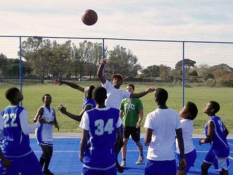 Jugendliche spielen Basketball im Walmer Township, Südafrika