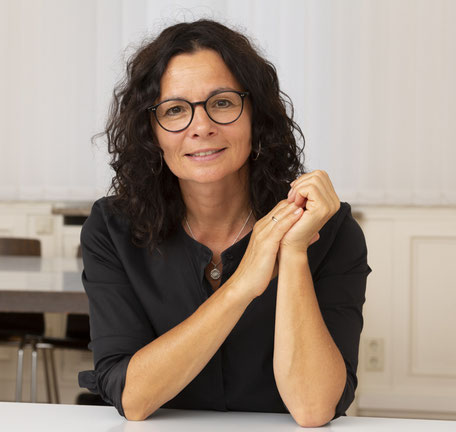 Foto von Ilona Rau mit schwarzer Bluse, sitzend an einem Tisch in einem Arbeitsraum mit den Hände vor dem Körper.