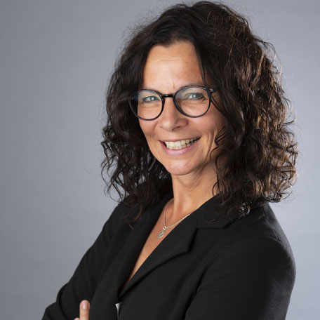 Foto von Ilona Rau im Profil mit schwarzer Brille, schwarzem Blazer, lächelnd in die Kamera blickend.