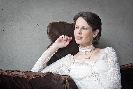 Model Ravienne Art im Brautkleid auf Sofa