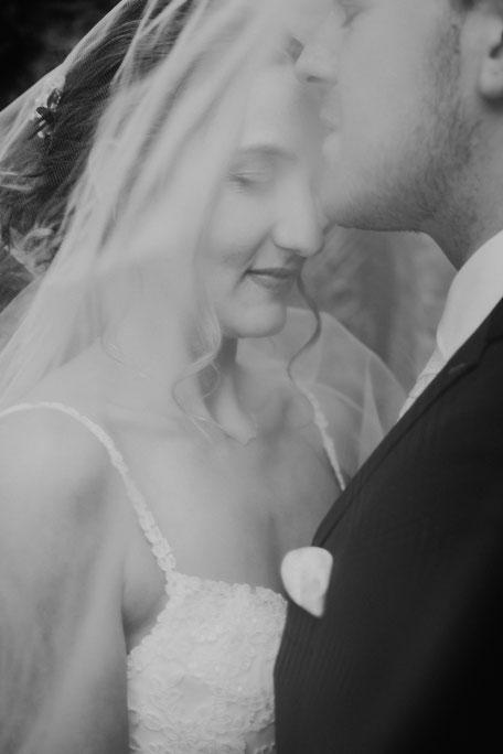 Bräutigam küsst Braut auf die Stirn unter dem Schleier