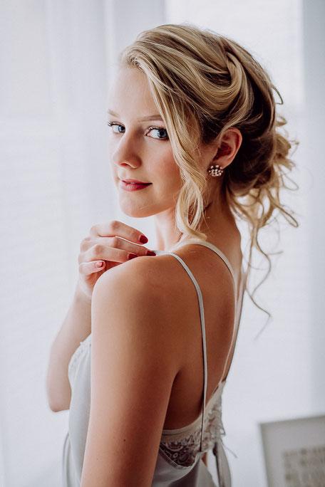 hübsche Braut steht in feiner Spitzenwäsche am Fenster in Mainz