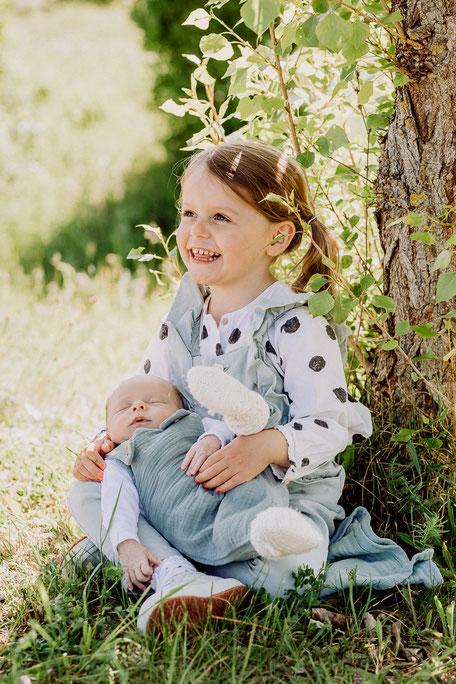 Schwester freut sich über das Baby auf ihrem Arm