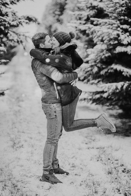 Mann umarmt Frau und hebt sie küssend hoch