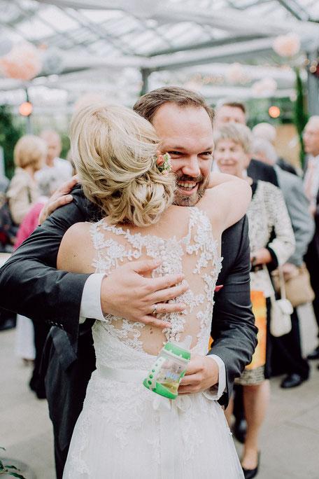 Braut wird von Gast umarmt bei Gratulationen nach Hochzeit