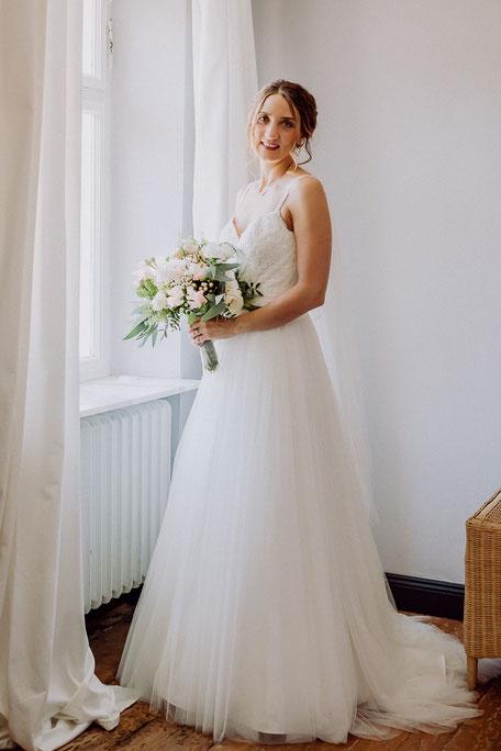 Braut steht im Brautkleid mit Brautstrauss vor dem Fenster im Schlossgut Diel