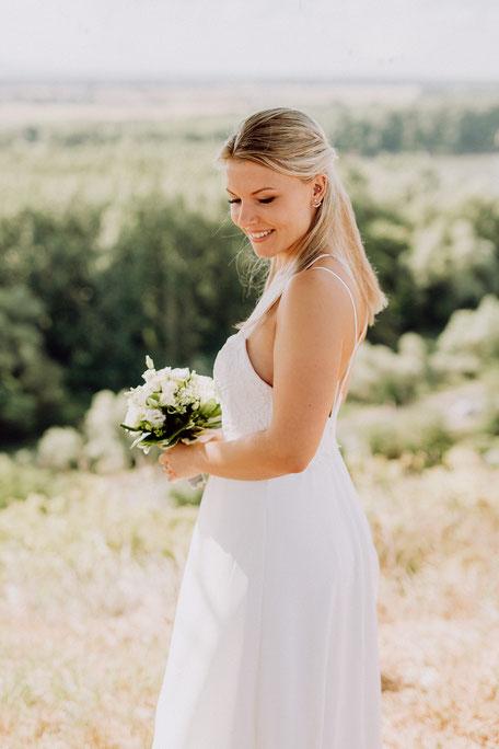 Braut im Brautkleid schaut lächelnd über ihre Schulter
