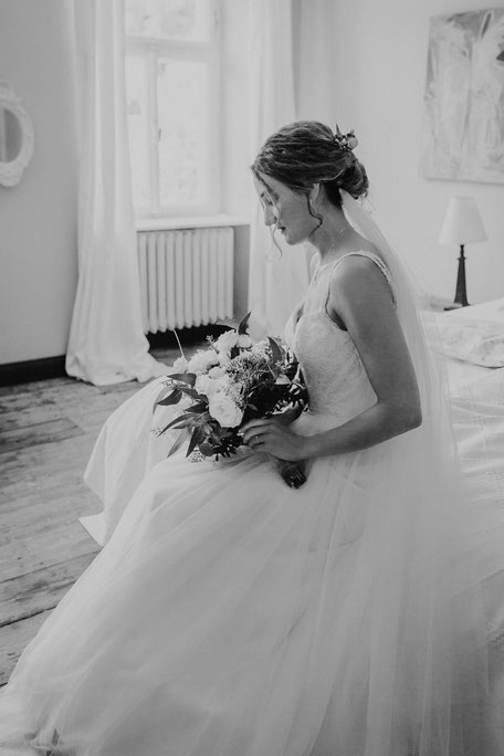 Die Braut sitzt mit Brautstrauss auf dem Bett und wartet auf den First Look