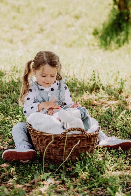 Schwester streichelt Baby über die Wange