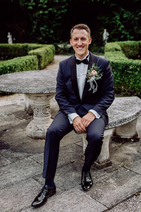 strahlender Bräutigam sitzt auf Bank