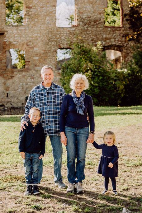 Oma und Opa mit Enkeln an der Hand lächeln