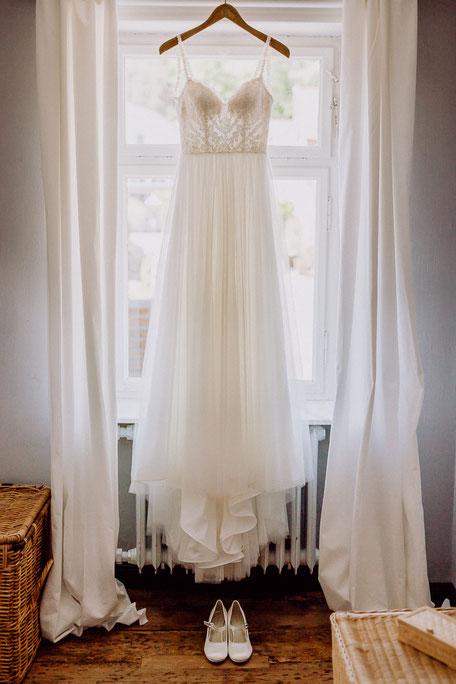Brautkleid mit Spaghettiträgern hängt am Fenster beim Ankleiden der Braut