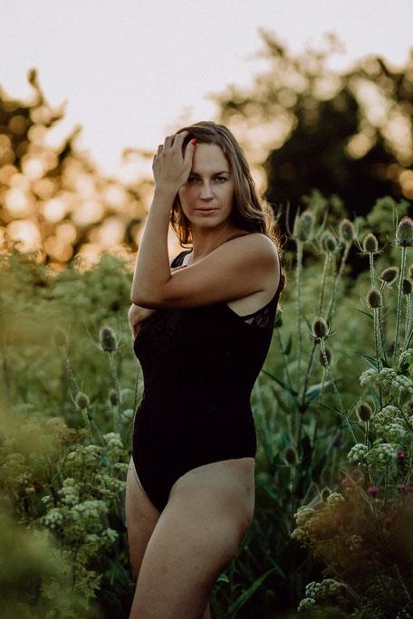 hübsche Frau steht in Wäsche in einem Feld