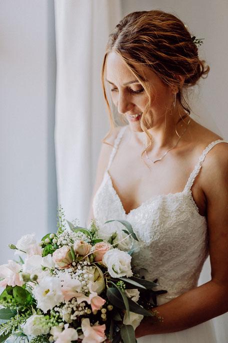 Die Braut schaut auf ihren Brautstrauss mit Eukalyptus