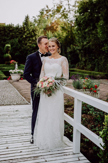 Bräutigam flüstert Braut ins Ohr