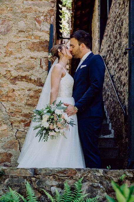 Braut und Bräutigam küssen sich vor der Hochzeit in Rümmelsheim